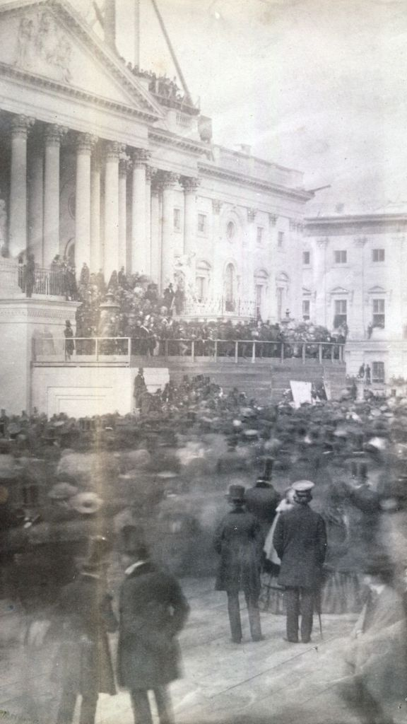 An early nineteenth century photograph of a crowd gathered outside a political building. People carry canes and wear top hats.