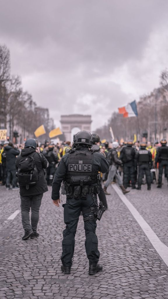 Under storm clouds on the Champs-Élysées, a police officer faces a crowd of people at a large demonstration. The Arc de Tiomphe in the background.